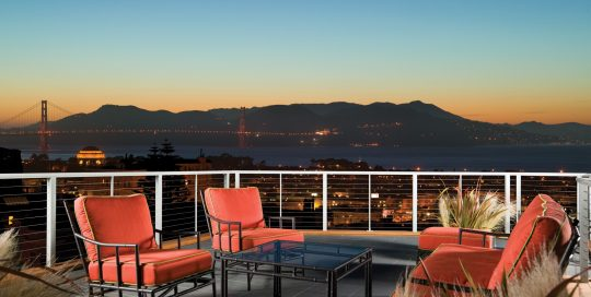 Rooftop deck in Pacific Heights neighborhood of San Francisco with custom cable railings and a view of the Golden Gate bridge at night