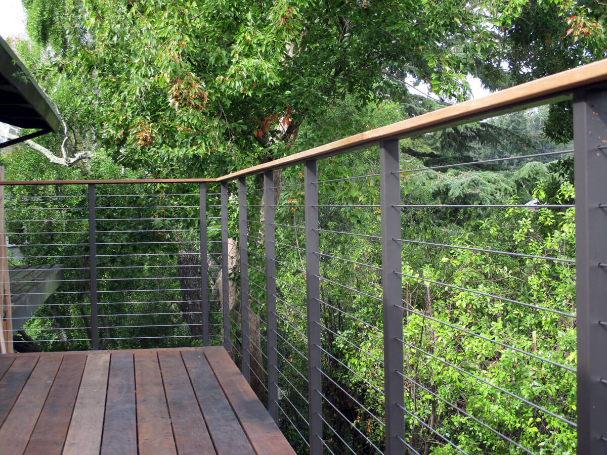 Steel cable railing installation with wooden handrails